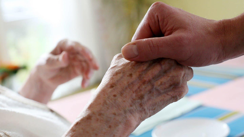 Eine pflegende Person hält die Hand eines alten Menschen (Foto: dpa Bildfunk, Picture Alliance)