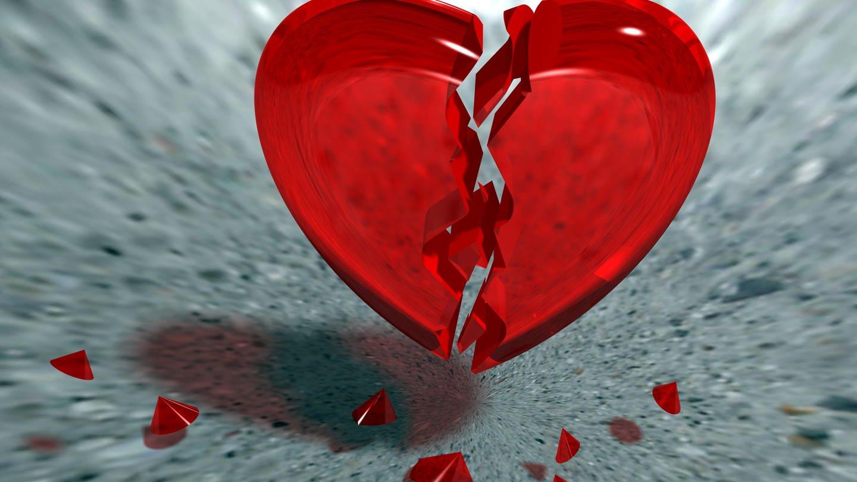 Gebrochenes Herz aus Glas, dass auf einem grauen Steinboden zerspringt