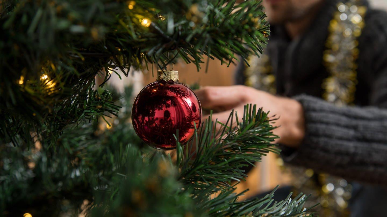 Ein Mann schmückt einen Weihnachtsbaum. (Foto: picture-alliance / Reportdienste, Picture Alliance)