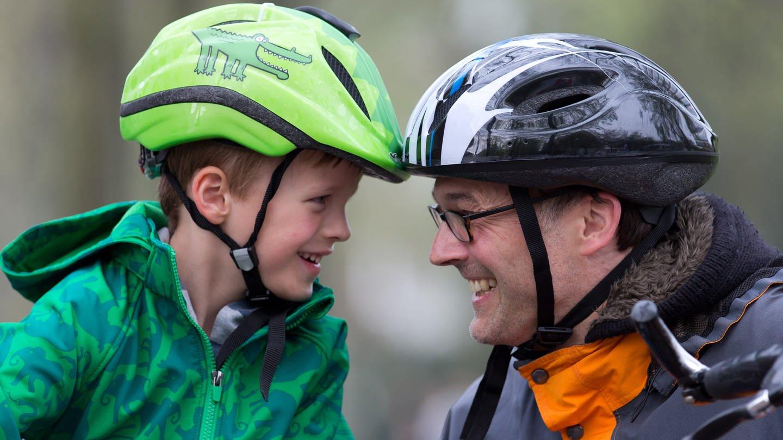 Ein Junge und ein Mann tragen Fahradhelme und lachen sich gegenseitig an (Foto: picture-alliance / Reportdienste, picture alliance / dpa | Friso Gentsch)