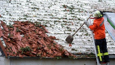 Feuerwehr kehrt Zeigel von kaputtem Dach (Foto: dpa Bildfunk, Peter Endig)
