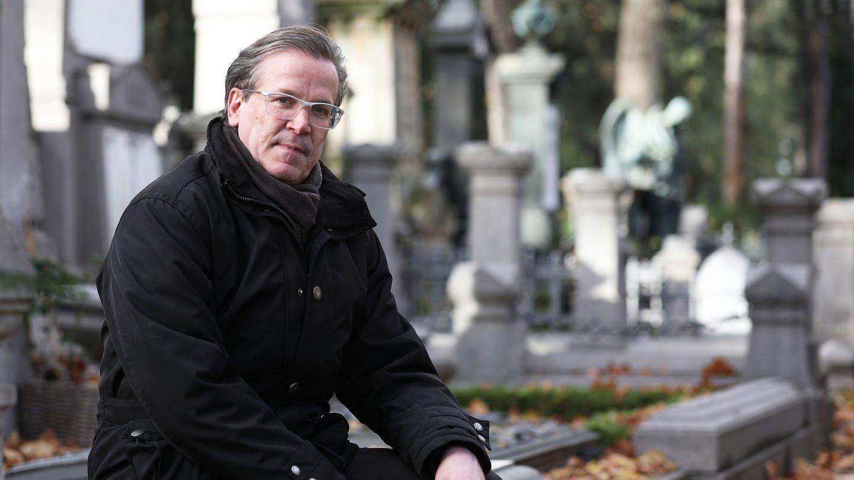 Christoph Kuckelkorn, Bestattungsunternehmer und Karnevalspräsident, sitzt auf dem Melatenfriedhof an Gräbern.