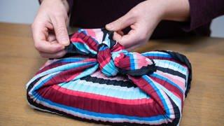 Eine Frau wickelt ein Geschenk mit der japanischen Furoshiki-Technik in ein Tuch ein  (Foto: picture-alliance / Reportdienste, Andrea Warnecke)