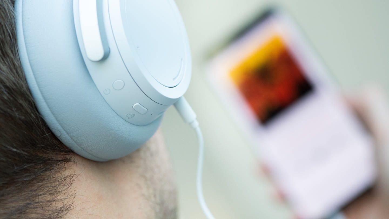 Ein junger Mann hört mit Kopfhörern Musik von seinem Smartphone. (Foto: dpa Bildfunk, picture alliance/dpa/dpa-tmn   Franziska Gabbert)