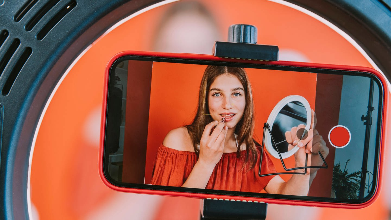 Teenage girl filming make-up tutorial at home