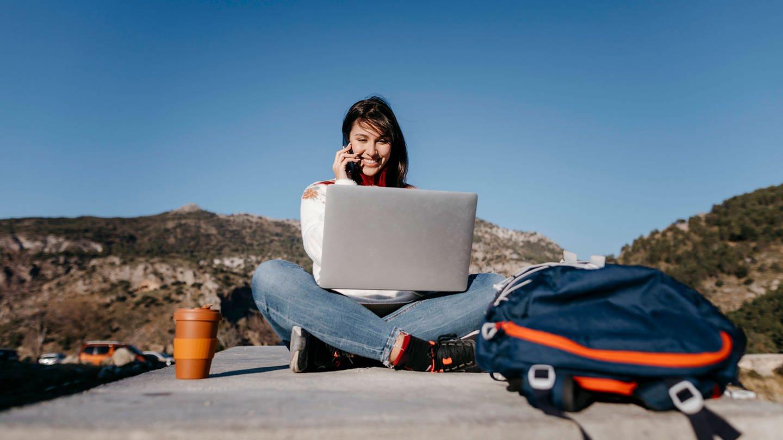 Lächelnde Frau am Handy während sie auf einer Mauer in der Sonne sitzt
