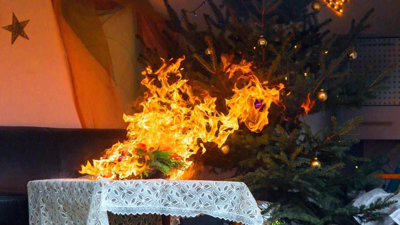 Adventskranz geht vor einem Weihnachtsbaum in Flammen auf. (Foto: Imago, Marius Schwarz)