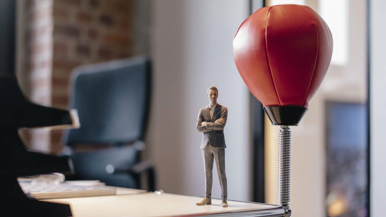 Businessman figurine standing on desk by punching ball model released Symbolfoto (Foto: Imago, imago images / Westend61)