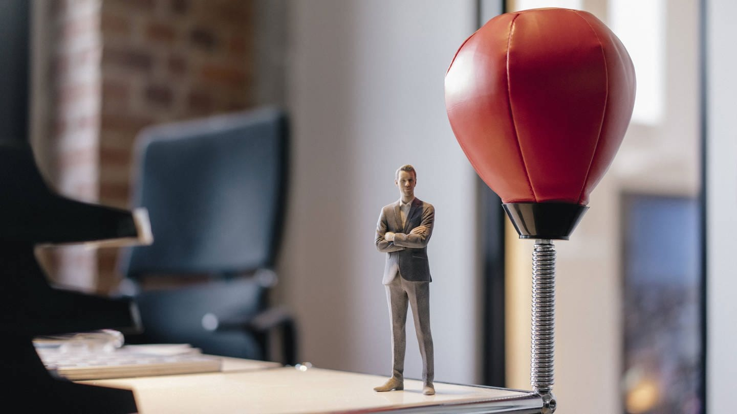 Businessman figurine standing on desk by punching ball model released Symbolfoto (Foto: Imago, Westend61)