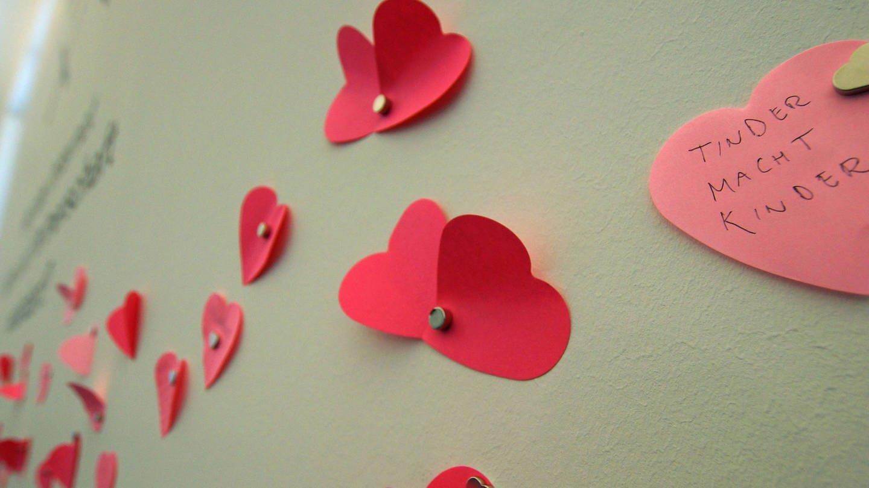 Herzchen Post-Its vor weißer Wand mit