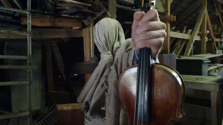 Eine in einem Sack verhüllte Person hält eine Violine in der Hand (Foto: Pressestelle, Brandlmayr)
