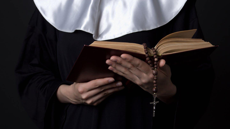 Nonne die Bibel in den Händen hält (Foto: Colourbox)