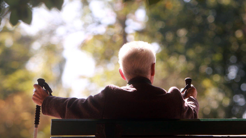 Älterer Mann mit Wanderstöcken genießt die warmen Temperaturen und den Sonnenschein auf einer Bank sitzend (Foto: Imago, Ralph Peters)