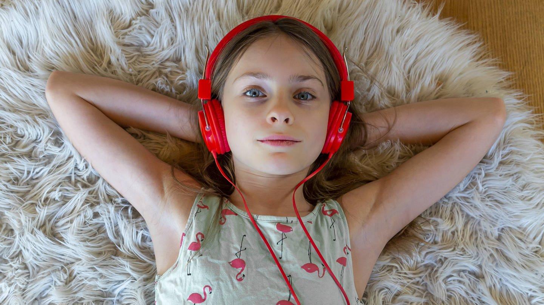 Ein Mädchen mit rotem Kopfhörern liegt auf dem Fußboden (Foto: Imago, Westend61)