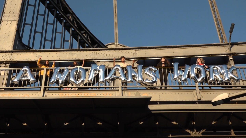 Schrift aus Luftballons an einer Brücke: