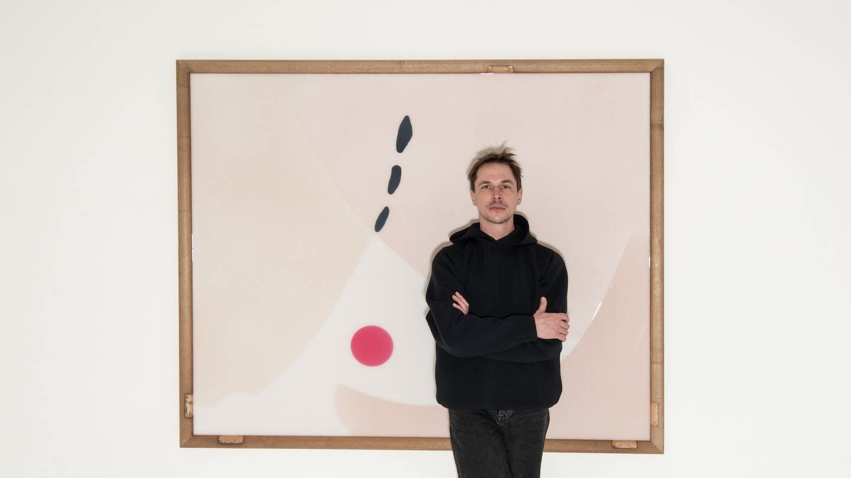 Porträt Thomas Lempertz (Im Hintergrund: ohne Titel, 180 x 150 cm, Acryl, Farbpigmente, Silikon auf Holz, Ballettstangen, 2021)