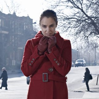 Woman wearing red coat standing at crossroad in gray city model released Symbolfoto (Foto: Imago, Westend61)