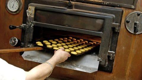 Bäcker schiebt ein Blech mit Plätzchen in den Ofen (Foto: Bernard Jaubert)