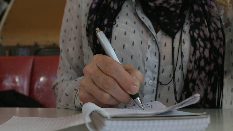 Frau schreibt ihre Erlebnisse in ihr Tagebuch
