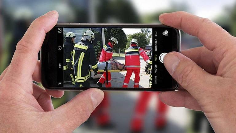 Zwei Hände halten ein Handy. Auf dem Bildschirm ein Foto von einem Rettungseinsatz. Im Hintergrund hinter dem Handy ist die gleiche Szene unscharf zu sehen. (Foto: SWR, Imago - Jochen Tack)