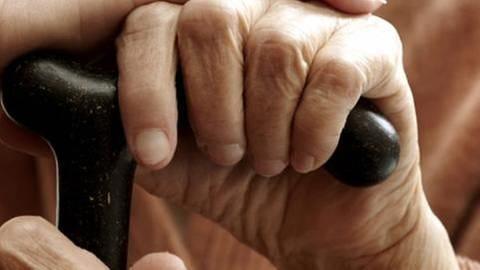 Seniorin hält ihren Gehstock