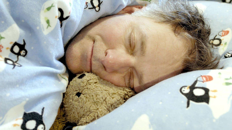 Mann schläft mit Teddy in Kinderbettwäsche (Foto: Imago, imago/Birgit Koch)