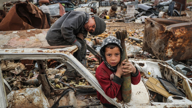 Ein Junge hält eine nicht explodierte Mörsergranate und sitzt auf einem ausgeschlachteten Auto auf einer Deponie für Munitions- und Artilleriereste (Foto: dpa Bildfunk, picture alliance/dpa   Anas Alkharboutli)