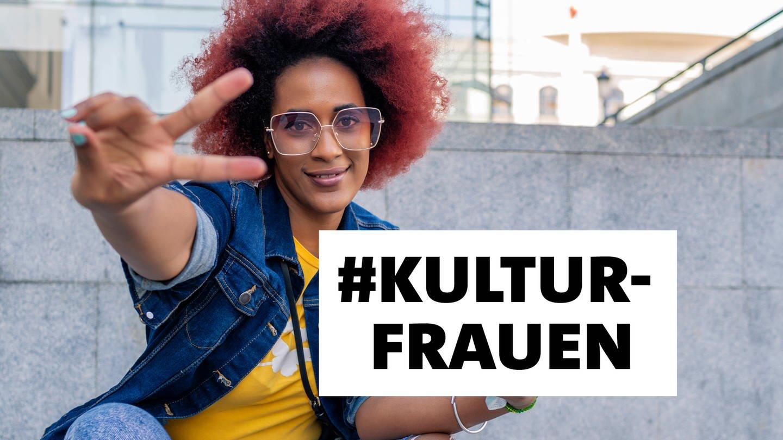 Junge Frau mit einem rot gefärbten Afro sitzt auf einer Treppe und zeigt das V-Zeichen mit der rechten Hand. Links hält sie ein Smartphone. Auf dem Bild ist ein Textblock #Kultufrauen, schwarze Schrift auf weißem Grund. (Foto: Imago, Imago / Cavan Images)