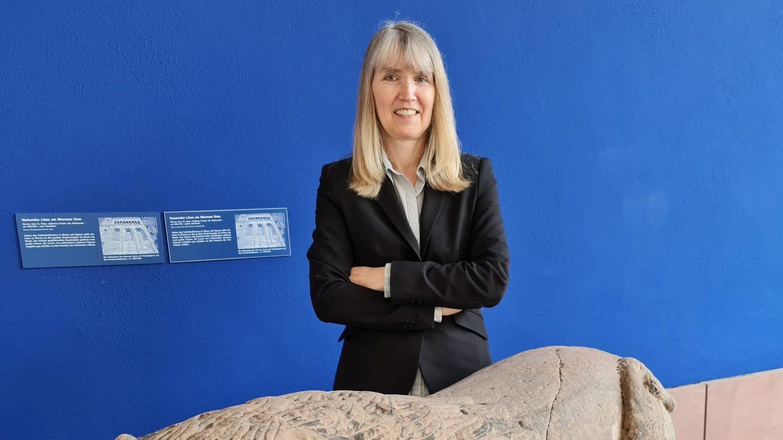 Birgit Heide, dunkel gekleidet mit grau-blonden, schulterlangen Haaren und Pony steht hinter einer mittelalterlichen Steinmetz-Skulptur eines Löwen. Der Hintergrund ist blau.