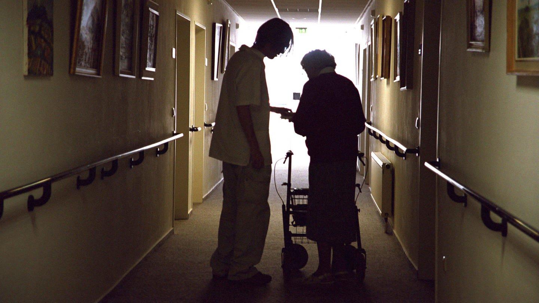 Symbolbild - Frau mit Gehhilfe und Pfleger