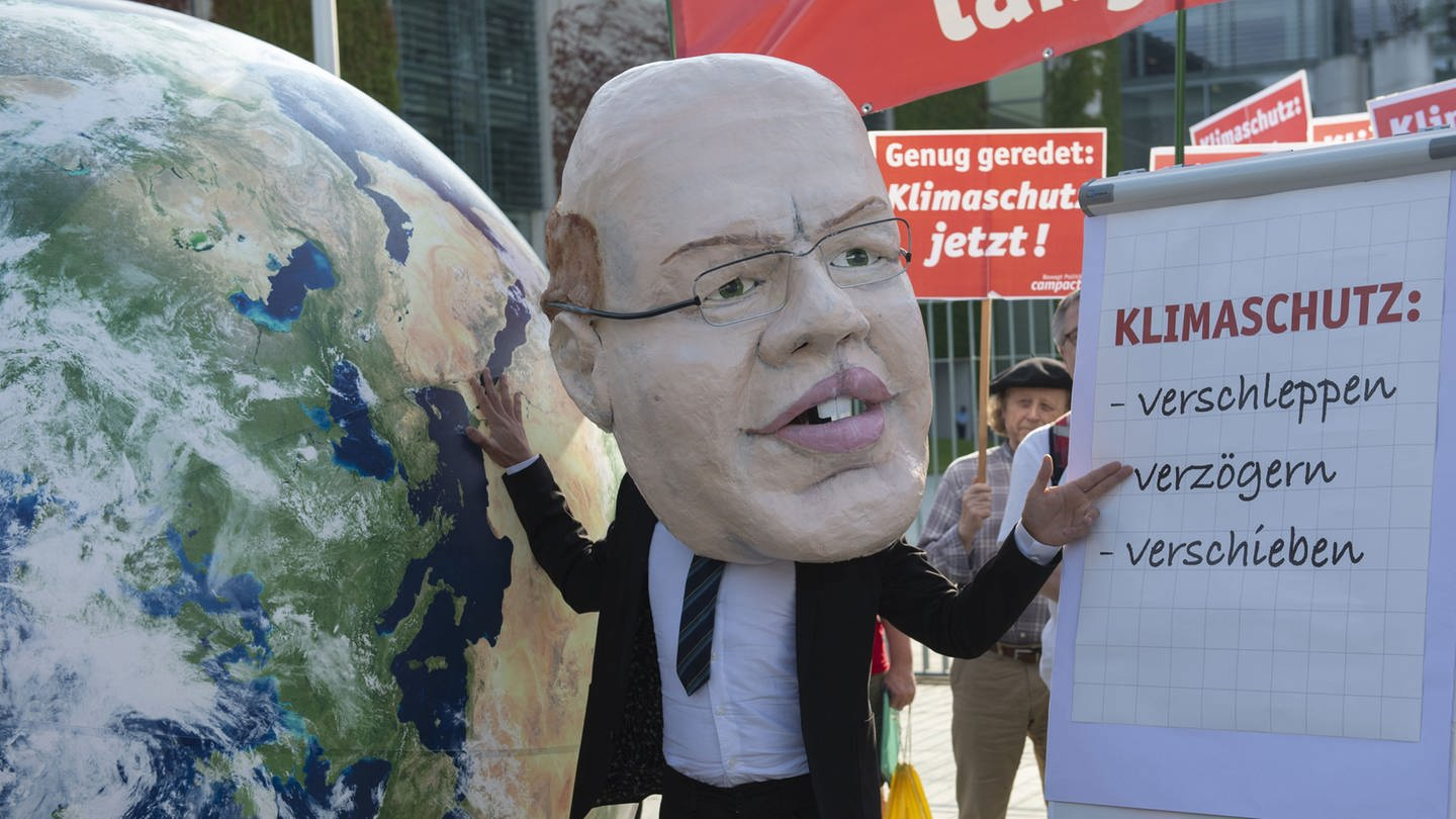 Demonstranten mit Transparenten und einer Maske von Bundeswirtschaftsminister Altmeier zum Thema Klimaschutz (Foto: picture-alliance / Reportdienste, picture alliance/Paul Zinken/dpa)