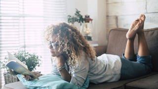 Frau liegt auf dem Sofa und liest  (Foto: Imago, Westend61)