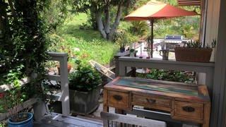 Kleiner Holz-Schreibtisch auf der Terrasse, Blick in den Garten mit alten Bäumen, Blumen und auf einen orange-farbenen Sonnernschirm (Foto: SWR, privat)
