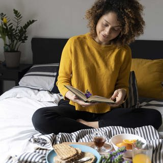 Women sitting on bed, having a healthy breakfast, reading book (Foto: Imago, imago)