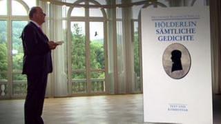 """Denis Scheck steht neben dem Buch """"Sämtliche Gedichte"""" von Friedrich Hölderlin (Foto: SWR, SWR -)"""