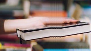 Jemand hält ein Buch in der Hand  (Foto: Imago, SWR, photocase)
