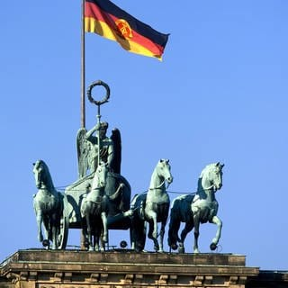 Quadriga mit DDR-Nationalflagge auf dem Brandenburger Tor in Berlin (Foto: Imago, imago images / SMID)