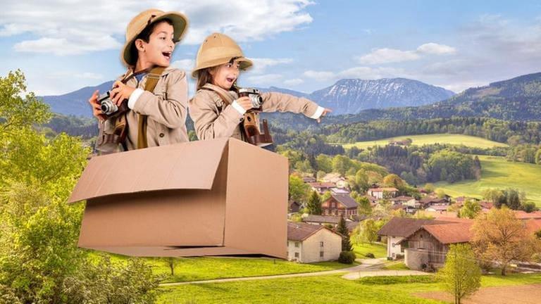 Kinder in fliegendem Karton über einem Alpendorf (Foto: Imago, imago/Panthermedia - luislourobd)