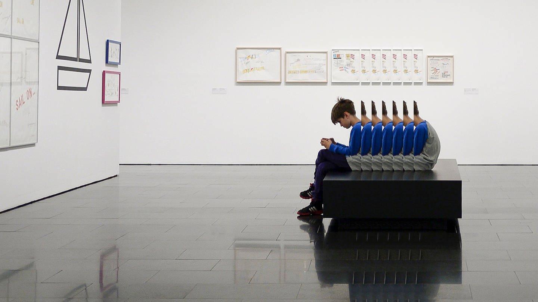 Junge sitzt im Museum