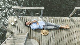 Ein Mann liegt entspannt auf einem Steg und hört Podcast (Foto: Imago, imago stock&people)