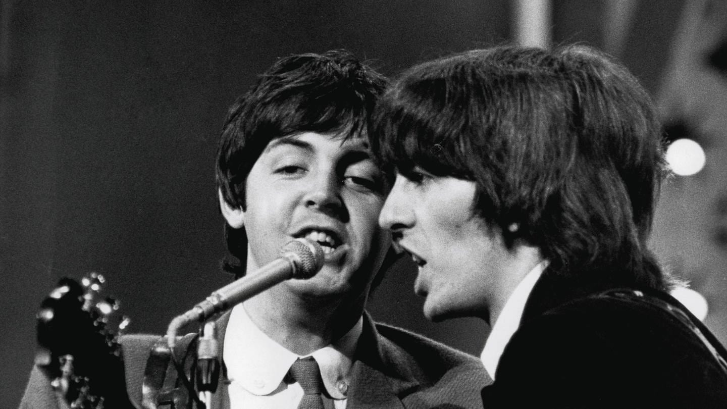 Die beiden Beatles Paul McCartney  und George Harrison singen im August 1965 (Foto: Imago, imago/Cinema Publishers Collection)