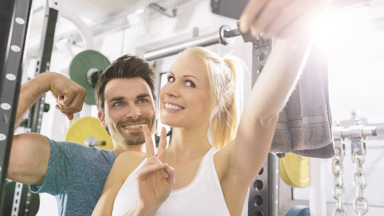 Junges Paar macht ein Selfie im Fitness-Studio: Teenager wetteifern um den perfekten Körper und posten Bilder in den sozialen Medien von möglichst dicken Muskeln oder möglichst dünnen Oberschenkeln (Foto: Imago, imago images / Westend61)