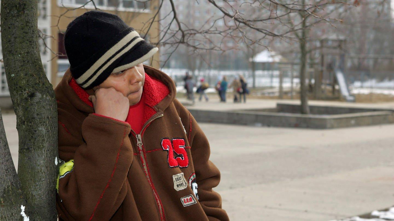 Ein türkischer Junge steht alleine auf einem Schulhof. Ausgrenzungserfahrungen können die Integration behindern. (Foto: Imago, imago images / Steffen Schellhorn)