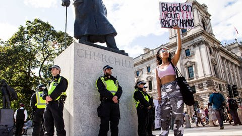 "Bei den #BlackLivesMatter- und Anti-Rassismus-Demonstrationen in London hält am 20. Juni 2020 eine Frau ein Plakat mit der Aufschrift ""Blood on your racist hands"" in die Höhe. Polizisten bewachen die Statue von Winston Churchill. (Foto: Imago, June 20, 2020, London, United Kingdom: A )"