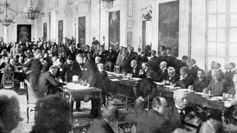 Unterzeichnung des Friedensvertrages mit Ungarn im Trianon in Versailles am 12. Juni 1920: Der italienische Botschafter in Paris setzt seine Unterschrift auf das Dokument (Foto: Imago, imago images / United Archives International)