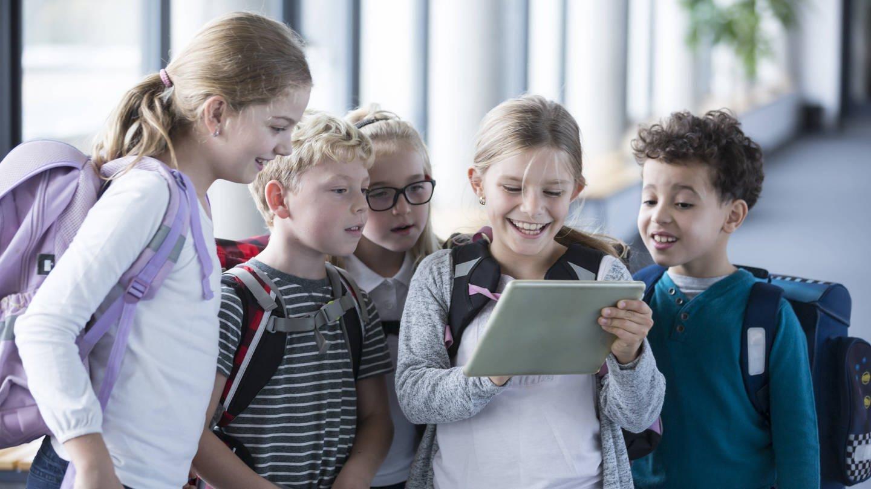 Kinder schauen im Schulkorridor in ein Tablet (Foto: Imago, imago/Westend61)