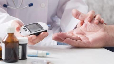 Eine Ärztin misst mit einem Gerät den Zuckerspiegel eines Patienten dem ein Blutstropfen aus dem Finger quillt (Foto: Getty Images, Thinkstock -)
