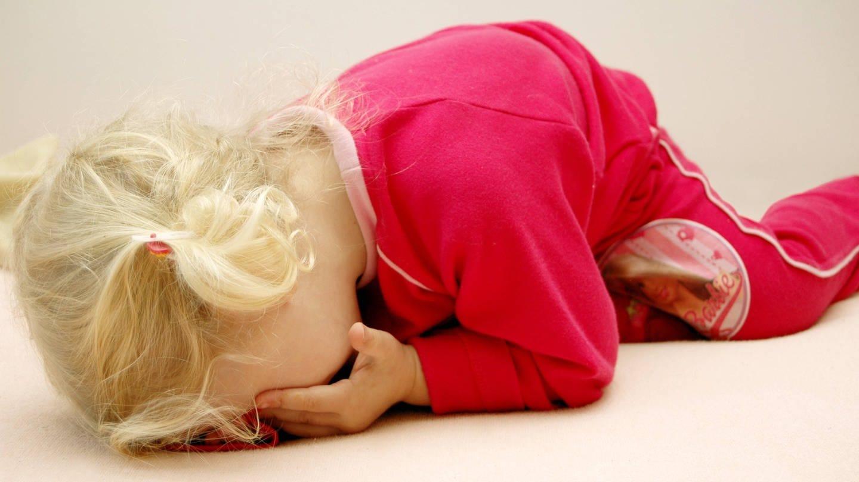 Kleines Mädchen liegt weinend auf dem Boden. Traumatische Erlebnisse können sich massiv auf Seele und Körper auswirken. Wissenschaftler erforschen unter anderem, wie sich traumatisierte Kinder entwickeln.