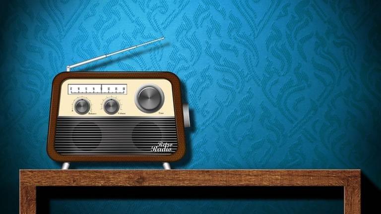 Ein altmodisches Radio mit Antenne steht auf einem Holztisch vor einer blauen Strukturtapete (Foto: Colourbox, Colourbox -)