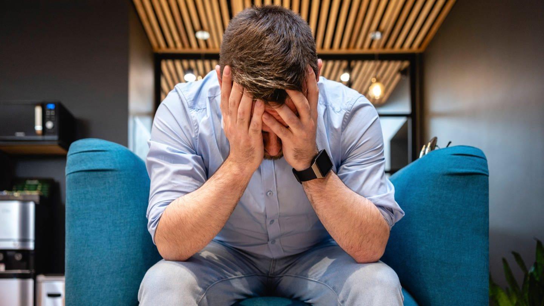 Mann stützt erschöpft den Kopf in die Hände: Die Zahl der Krankheitstage aufgrund psychischer Probleme hat stark zugenommen. Allein 2019 waren 2,2 Millionen Menschen betroffen.